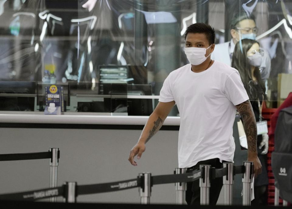 Pyae Lyan Aung, a member of the Myanmar national team who raised a three-finger salute during a qualifying match for the 2022 World Cup in late May, arrives at Kansai International Airport in Osaka Prefecture, Japan on Wednesday June 16, 2021. Pyae Lyan Aung has refused to return home and is seeking asylum, a request the government was considering taking into account unrest in his country following a coup. (Kyodo News via AP)