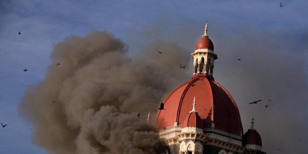 Smoke billows from under the main dome of the Taj Palace Hotel in Mumbai on 27 November 2008.