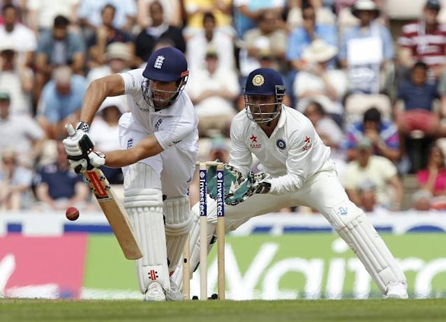 England's Captain Alastair Cook (left) hits a shot watched by India's Captain and wicketkeeper MS Dhoni during their first day of the third Test match at the Ageas Bowl ground in Southampton on July 27, 2014 (AFP Photo/Ian Kington)
