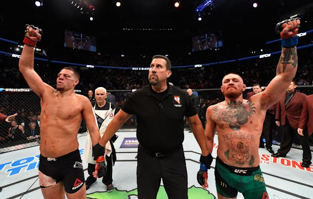 Conor McGregor and Nate Diaz raise their hands and wait to hear the judges decision after their welterweight bout during the UFC 202 event at T-Mobile Arena on Aug. 20, 2016 in Las Vegas. (Getty Images)