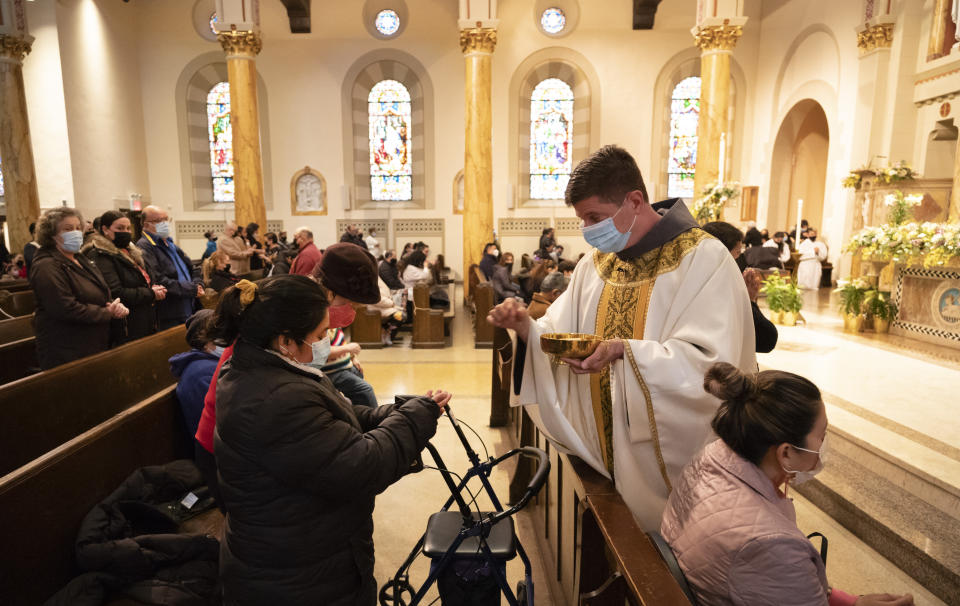 Rev. Russels Governale serves communion during a Spanish-language Easter service at St. Bartholomew Roman Catholic Church, Sunday, April 4, 2021, in New York. The parish has lost 80 members to COVID-19. (AP Photo/Mark Lennihan)
