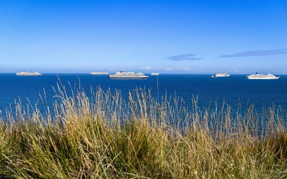 A number of cruise ships are anchored off the Dorset coast, where they have remained since last spring - Getty