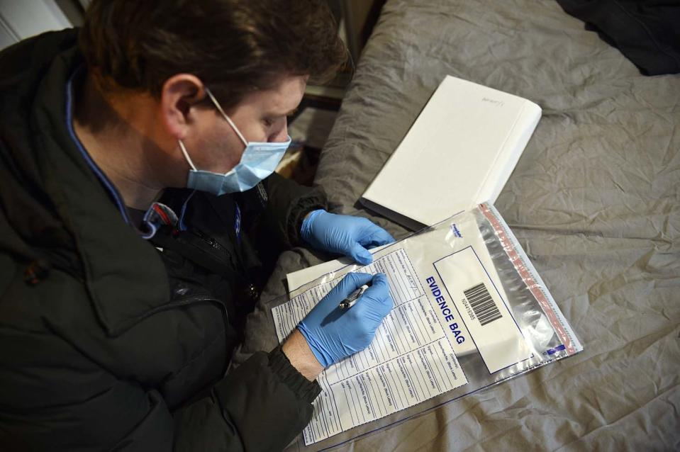 A Thames Valley Police officer gathers evidence during a search in Bracknell this month