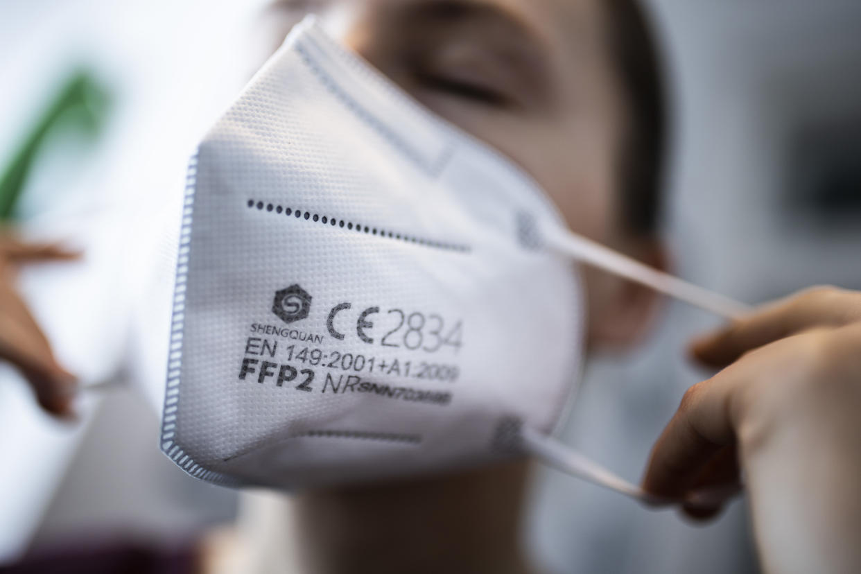 BERLIN, GERMANY - JANUARY 15: A woman puts on a FFP2 face mask  on January 15, 2021 in Berlin, Germany. In Germany there is a discussion about the obligation to wear a ffp2 masks in public. (Photo by Florian Gaertner/Photothek via Getty Images)