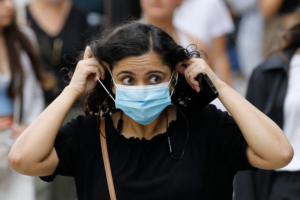 A shopper adjusts her face mask on Oxford Street om London on July 24, 2020, after wearing facemasks in shops and supermarkets became compulsory in England as a measure to combat the spread of the novel coronavirus. (Photo by Tolga AKMEN / AFP) (Photo by TOLGA AKMEN/AFP via Getty Images)