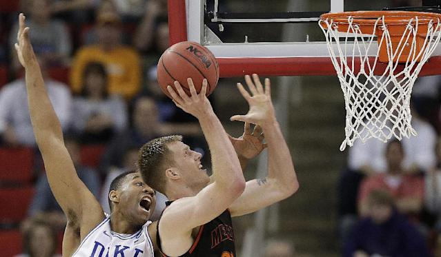 Mercer forward Jakob Gollon (20) heads to the hoop as Duke forward Jabari Parker (1) defends during the second half of an NCAA college basketball second-round game, Friday, March 21, 2014, in Raleigh, N.C