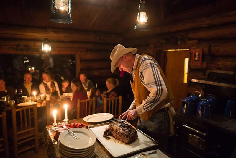 Guests are served an amazing dinner in the cabin after taking the sleigh ride up the mountain. | Courtesy of Lone Mountain Ranch