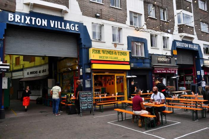 Empty tables are seen during a quiet night at Brixton Village in London