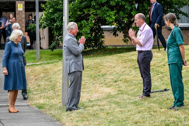 The Prince of Wales remains socially distanced as he a performs a namaste to Professor Mark Pietroni during a hospital visit. (PA Images)