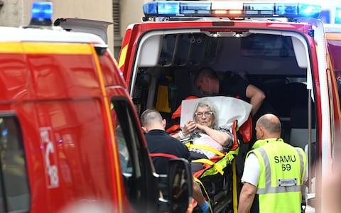 Emergency workers stretcher a woman to a waiting ambulance after a suspected package bomb blast along a pedestrian street in the heart of Lyon, southeast France - Credit:  PHILIPPE DESMAZES/AFP
