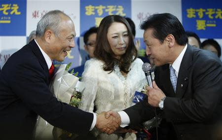 Japan's former health minister Yoichi Masuzoe (L) shakes hands with his supporter at his office, following local media reports that he is certain to be elected as the new Tokyo Governor, in Tokyo February 9, 2014. REUTERS/Yuya Shino