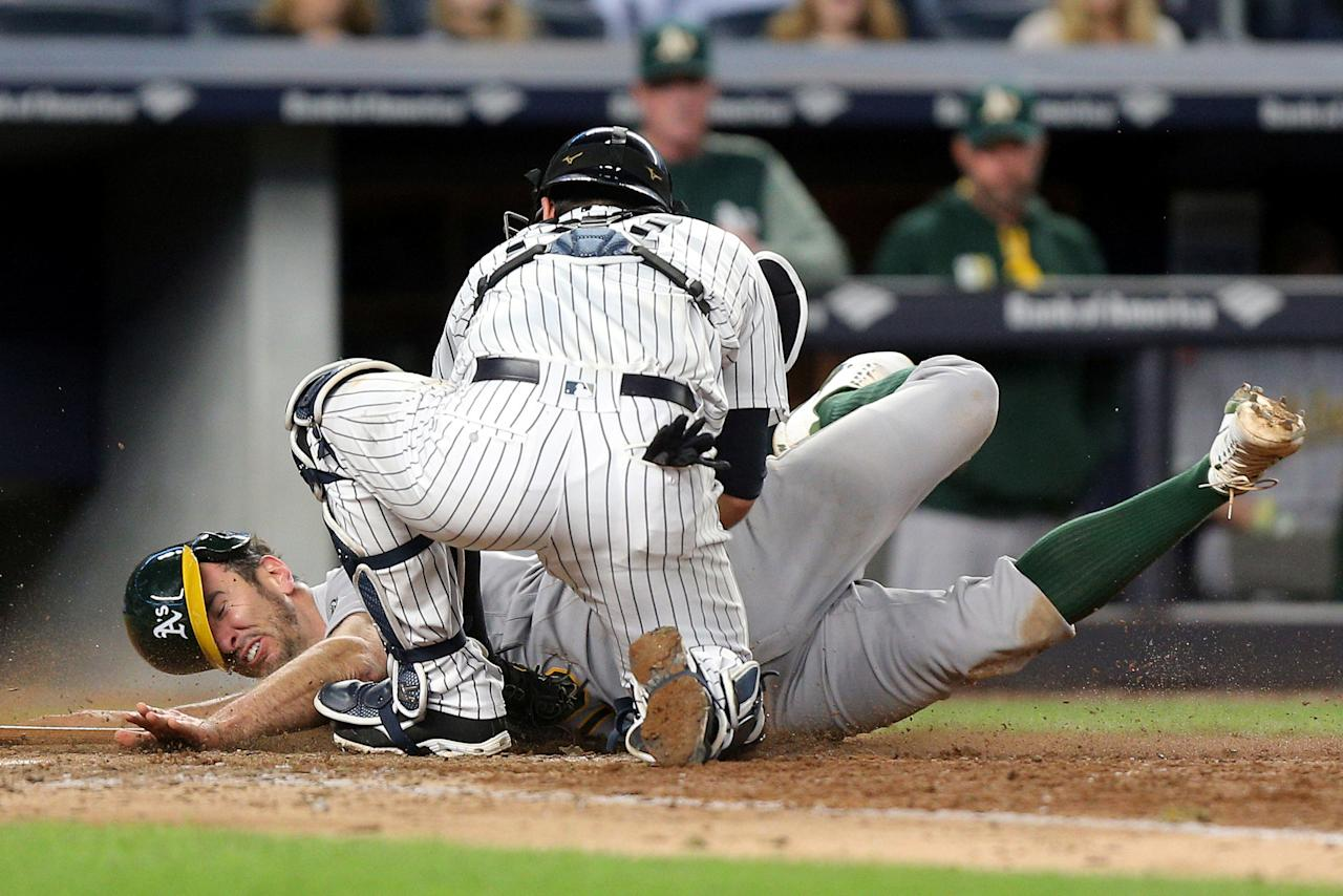 May 26, 2017; Bronx, NY, USA; Oakland Athletics shortstop Adam Rosales (16) is tagged out by New York Yankees catcher Austin Romine (27) while trying to score on a ground ball by Oakland Athletics center fielder Rajai Davis (not pictured) during the eighth inning at Yankee Stadium. Mandatory Credit: Brad Penner-USA TODAY Sports     TPX IMAGES OF THE DAY