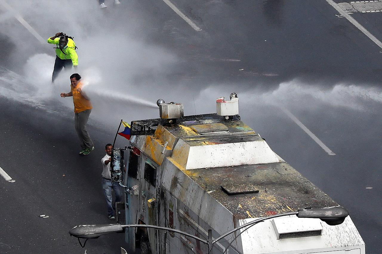 Opposition Deputy Carlos Paparoni is hit by a jet of water during riots at a march to the state ombudsman's office in Caracas Venezuela
