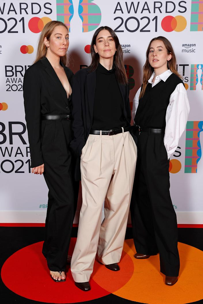 Styled by Rebecca Grice, the sister trio was dressed in very elegant and understated looks from The Row, of course. Este wore a black suit, belted at the waist. Danielle's look consisted of a black blazer and top, paired with khaki trousers. Alana wore a loose-fitting white shirt and flared pants, topped with a black sweater vest.