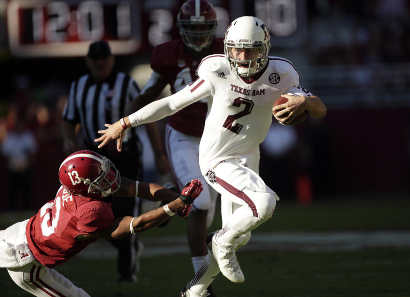 FILE - In this Nov. 10, 2012 file photo, Texas A&M quarterback Johnny Manziel (2) runs through the tackle of Alabama defensive back Deion Belue (13) during the first half of an NCAA college football game at Bryant-Denny Stadium in Tuscaloosa, Ala. Manziel has pleaded guilty to a misdemeanor charge stemming from his arrest last year for fighting outside a bar near campus. The Heisman Trophy winner made a brief appearance in court Monday, July 15, 2013 in College Station, Texas, and admitted he failed to identify himself to police following the altercation in June 2012. (AP Photo/Dave Martin, File)