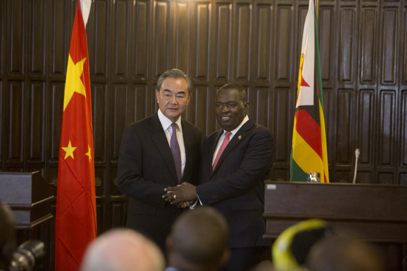 Chinas Foreign Minister Wangi Yi, left, greets Zimbabwe's Foreign minister Sibusiso Moyo after a joint press conference in Harare, Zimbabwe, Sunday, Jan, 12, 2020. Wangi Yi is in Zimbabwe as part of a five nation tour of Africa that seeks to promote the Asian economic and political interests on the continent. (AP Photo/Tsvangirayi Mukwazhi)