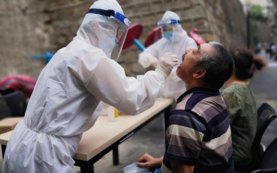 vA medical worker swabs throat of a citizen during the outbreak in Urumqi, Xinjiang - Shi Yujiang/China News Service via Getty Images