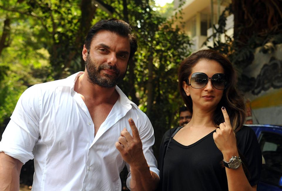 Indian Bollywood actor Sohail Khan (L) poses with his wife Seema Khan after voting in national elections at a polling station in Mumbai on April 24, 2014. India's 814-million-strong electorate is voting in the world's biggest election which is set to sweep the Hindu nationalist opposition to power at a time of low growth, anger about corruption and warnings about religious unrest.   AFP PHOTO/STR        (Photo credit should read STRDEL/AFP via Getty Images)