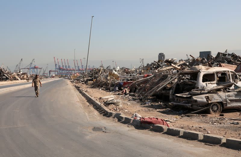 A Lebanese army soldier walks past debris and damaged vehicles at Beirut port