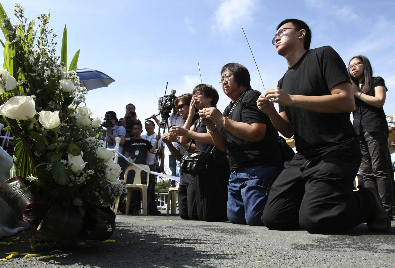 Relatives and a survivor in the botched bus hostage drama in Manila last year, hold incense during a Buddhist ceremony to mark the first anniversary at the site Tuesday Aug. 23, 2011 at the Rizal Park in Manila, Philippines. Eight Hong Kong tourists were killed in the botched hostage rescue when a dismissed policeman took them hostage exactly a year ago Tuesday. They are from right, survivor Lee Ying Chuen, Tse Chi Hang, Lee Mei Chun, Lin Siu Ching, Tse Chi Kin, all relatives of Masa Tse, the tour guide who was the first to be killed by the hostage-taker. (AP Photo/Bullit Marquez)