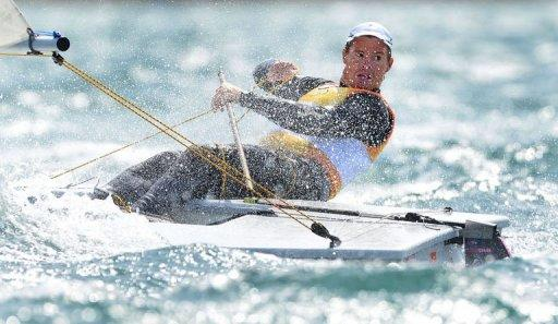 Australia's Tom Slingsby looks back at his rivals as he wins gold in the Laser sailing class at the London 2012 Olympic Games, in Weymouth