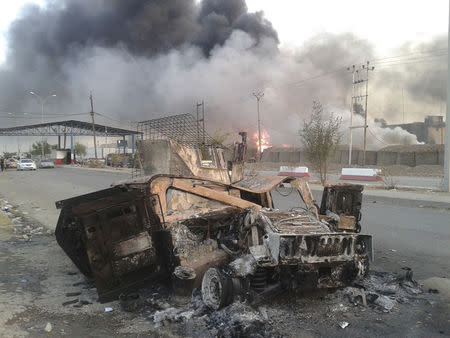 A burnt vehicle is seen during clashes between Iraqi security forces and al Qaeda-linked Islamic State in Iraq and the Levant (ISIL) in the northern Iraq city of Mosul