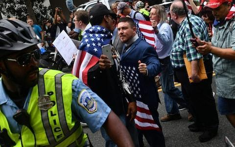 <span>Jason Kessler, escorted by police during his August 12 rally outside the White House</span> <span>Credit: AFP </span>