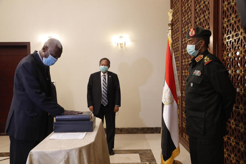 Maj. Gen. Yassin Ibrahim Yassin, left, takes the oath as Minister of Defense in front of Gen. Abdel-Fattah Burhan, head of the ruling sovereign council, right, in the presence of Prime Minister Abdalla Hamdok, center, at the Presidential Palace in Khartoum, Sudan, Tuesday, June 2, 2020. The ceremony came more than two months after the death of the former defense chief and amid tensions with neighboring Ethiopia. (AP Photo/Marwan Ali)