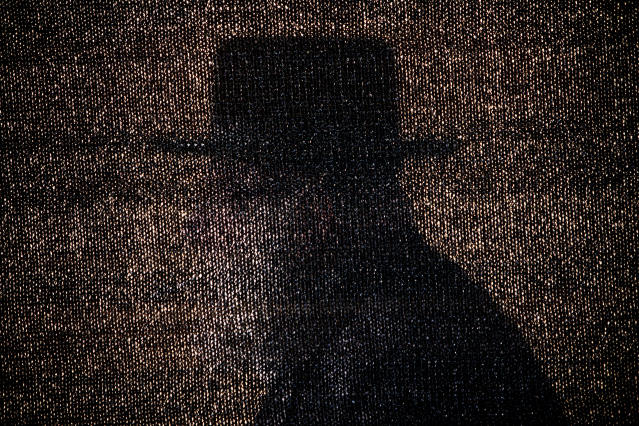 <p>An Ultra-Orthodox Jewish man is seen through a net during Siyum Ha'Shas, a celebration marking the completion of the learning cycle of the Babylonian Talmud — a collection of oral Jewish laws and traditions passed down from generation to generation — in Jerusalem, July 31, 2012. (Photo: Oded Balilty/AP) </p>