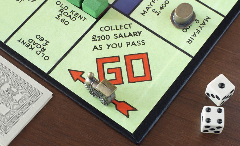 """Durham, England - December 31, 2011: The British version of the Monoploy board has famous streets and areas of London. """"GO"""" is the first stop of the board. Visible are some Monopoly money and dice and marks. Monopoly is a board game published by Parker Brothers"""