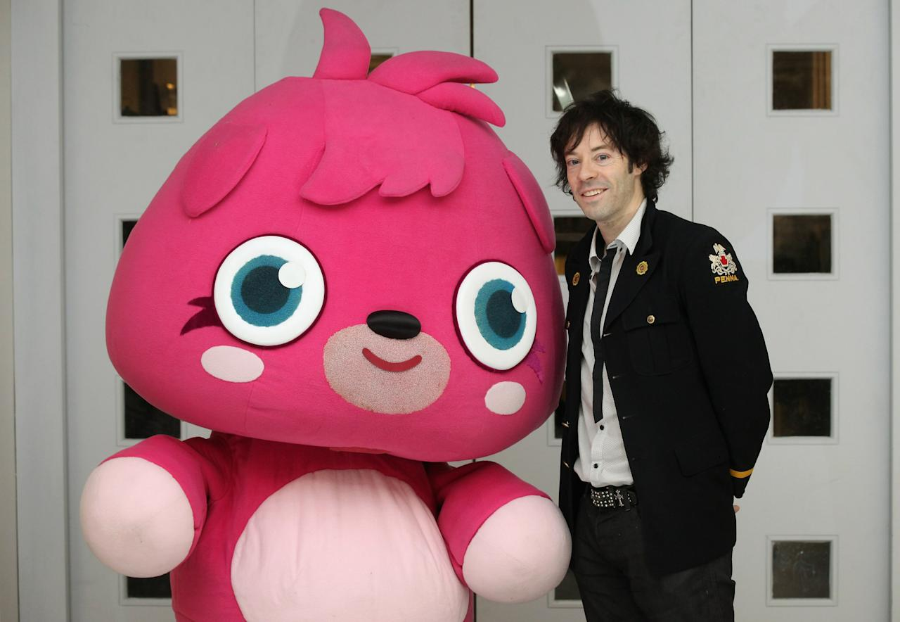 """LONDON, ENGLAND - FEBRUARY 22:  Michael Acton-Smith, the CEO of Mind Candy, poses for a photograph with Poppet outside a pop-up shop selling merchandise from the children's online game """"Moshi Monsters"""" in Whiteleys Shopping Centre on February 22, 2011 in London, England. moshimonsters.com has over 34 million users, it is aimed at the 7-12 year old who adopt and look after pet monsters. Players must solve educational puzzles to accumulate currency, known as Rox, which can be used to buy food and gifts for their monster. The store is open throughout February school half-term and offers activities and merchandise to Moshi Monsters players..  (Photo by Oli Scarff/Getty Images)"""