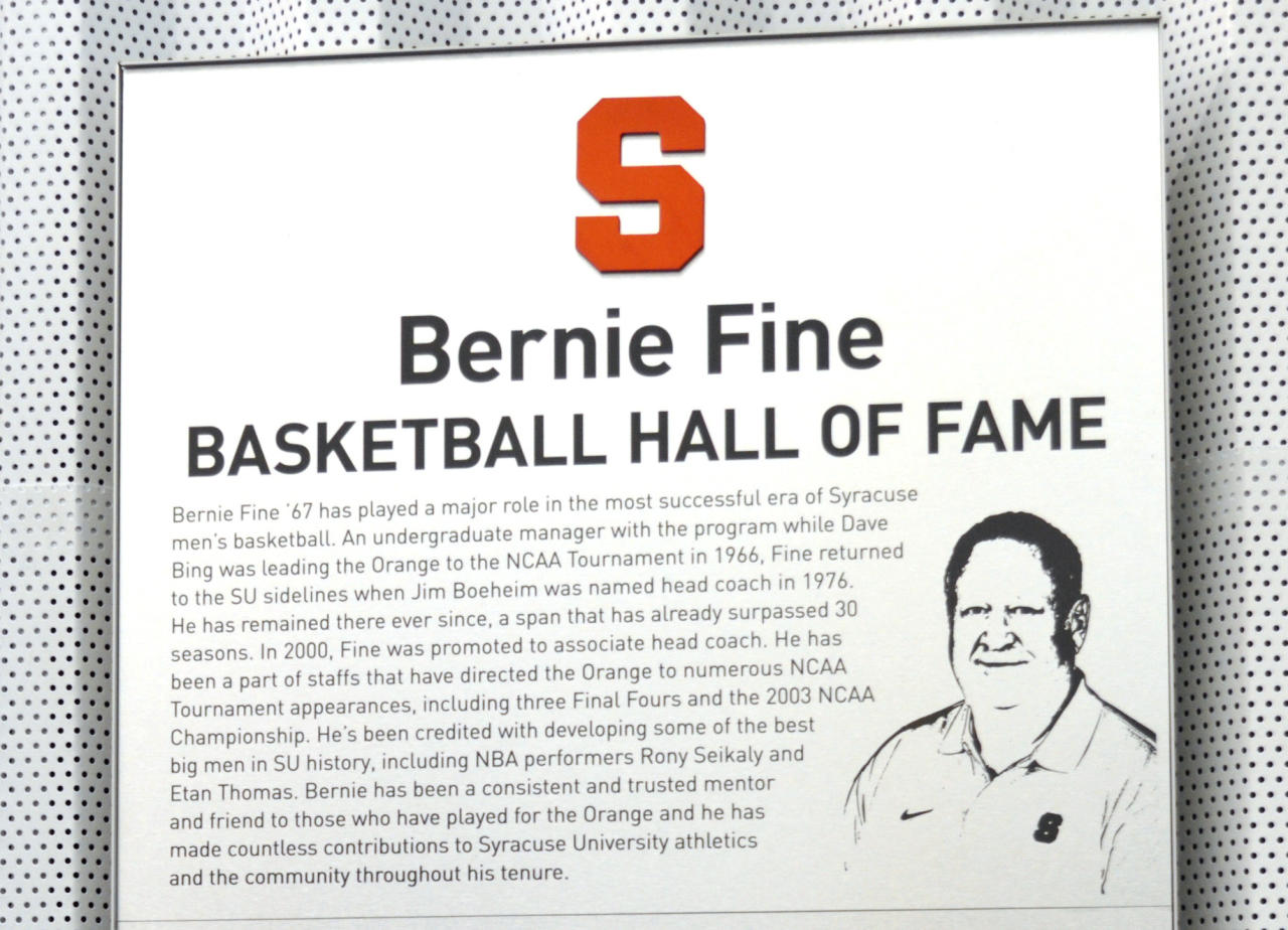 A plaque honoring Bernie Fine, Syracuse University men's basketball associate coach, hangs in the Syracuse University practice facility in Syracuse, N.Y., Friday, Nov. 18, 2011. Fine was placed on administrative leave, Thursday, Nov. 17, after old child molesting allegations resurfaced. (AP Photo/Kevin Rivoli)