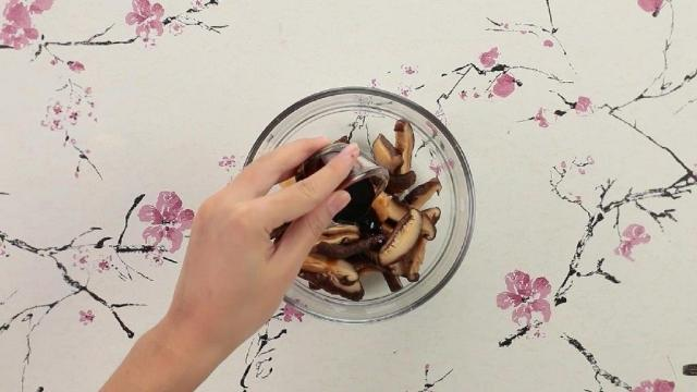 Adding oyster sauce to mushrooms in a bowl