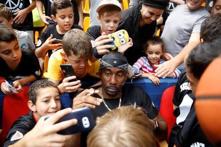 "Former NBA player Amar'e Stoudemire (C) signs autographs during a workshop for youth entitled ""Amar'e Stoudemire 2016 Basketball Peace Camp"", days after arriving in Israel to play for Hapoel Jerusalem Basketball Club, in Jerusalem August 8, 2016. REUTERS/Ronen Zvulun"