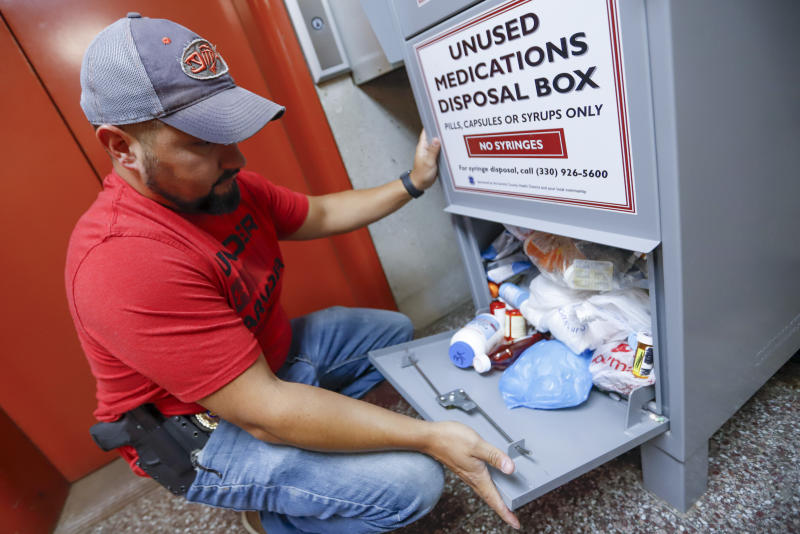 FILE - In this Sept. 11, 2019, photo, narcotics detective Paul Laurella retrieves unused medications from the police department's disposal box in Barberton, Ohio. Jury selection is set to begin Wednesday, Oct. 16, 2019, in the first federal trial over the nation's opioid epidemic. (AP Photo/Keith Srakocic, File)