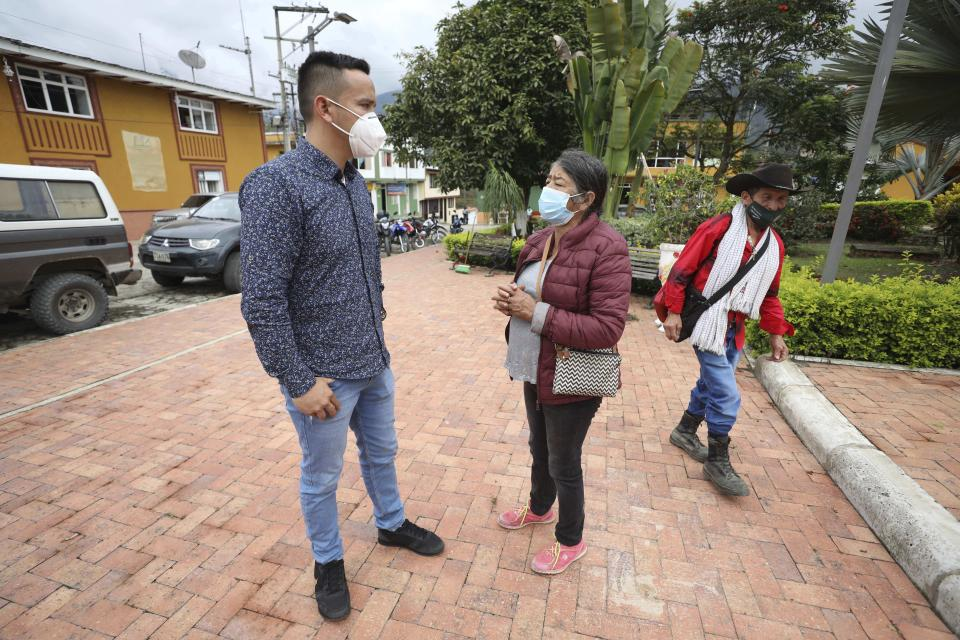 Wearing masks to curb the spread of the new coronavirus, Mayor Jaime Rodriguez, left, talks with a resident in Campohermoso, Colombia, Thursday, March 18, 2021. Rodriguez has been the only town resident to contract COVID-19 when he travelled to the Capital of Colombia, Bogota, but he had to stay there until he recovered to avoid spreading the disease in his home town. (AP Photo/Fernando Vergara)
