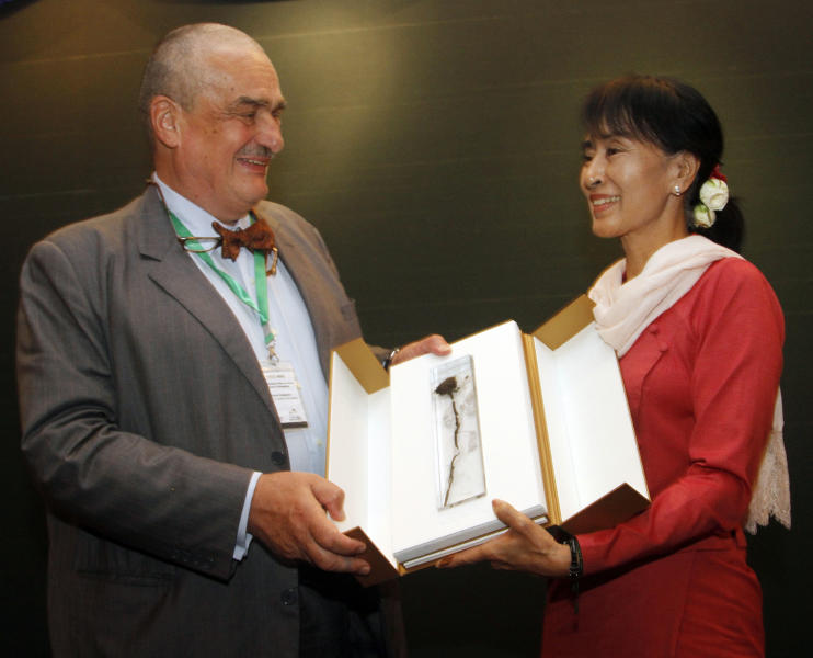 Myanmar opposition leader Aung San Suu Kyi, right, receives a posthumous gift from Foreign minister of Czech Republic Karel Schwarzenberg, left, during their meeting at Thingaha hotel in Naypyitaw, Myanmar, Tuesday, July 17, 2012. The visiting Foreign minister of Czech Republic Karel Schwarzenberg handed over a posthumous gift from the late Vaclav Have to fellow Nobel peace laureate Aung San Suu Kyi in the administrative capital of Naypyitaw Tuesday. Schwarzenberg arrived here Monday for a 4-day visit to Myanmar. (AP Photo/Khin Maung Win)