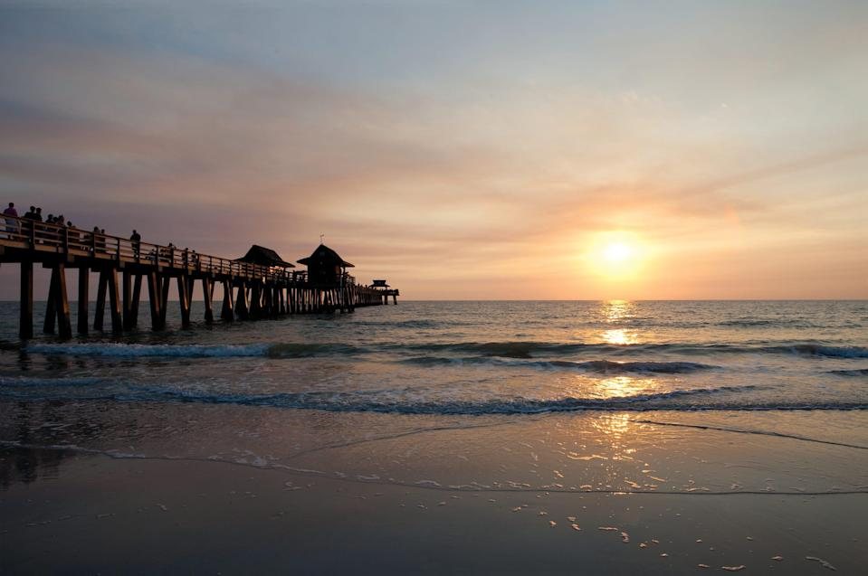 The sun sets over the Gulf of Mexico and Naples Pier, a free attraction for fishing, strolling or just relaxing.