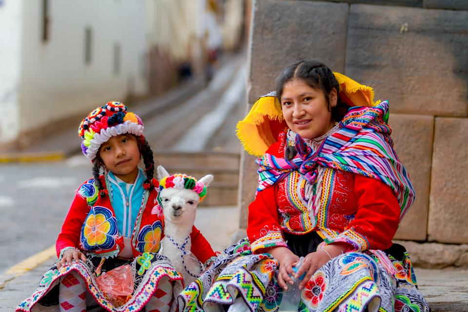 Cusco, Peru - February 10, 2018: Young woman with her little niece pose in a portrait with their typical costumes next to her little alpaca in a street in the historic center of Cusco