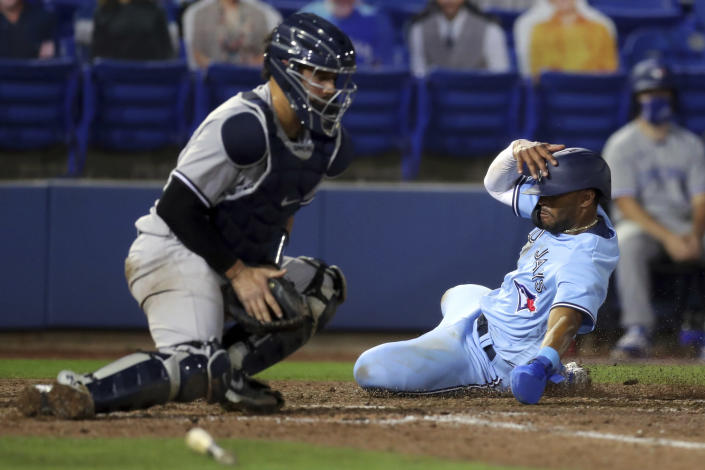 Toronto Blue Jays' Josh Palacios slides in to score next to New York Yankees catcher Gary Sanchez during the eighth inning of a baseball game Tuesday, April 13, 2021, in Dunedin, Fla. The Blue Jays won 7-3. (AP Photo/Mike Carlson)