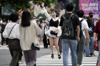 A woman wearing a protective mask to help curb the spread of the coronavirus jumps at Shibuya pedestrian crossings Monday, Sept. 21, 2020, in Tokyo. The Japanese capital confirmed more than 90 coronavirus cases on Monday marking Respect-for-the-Aged Day holiday. (AP Photo/Eugene Hoshiko)