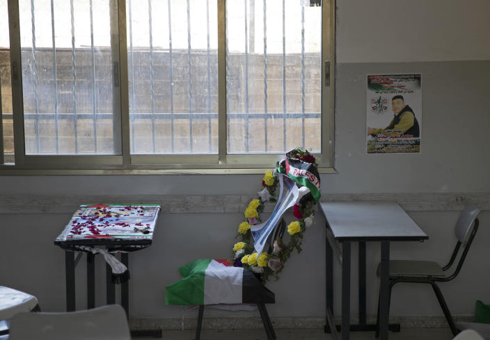A poster of 17-year-old Palestinian Mohammad Hamayel, and a memorial wreath adorn his classroom in the village of Beita, south of the West Bank city of Nablus. Monday, June 14, 2021. Hamayel was killed during clashes with Israeli forces following a protest against the wildcat Jewish settlement of Eviatar that was established last month without the permission of Israeli authorities on land the Palestinians say is privately owned. (AP Photo/Majdi Mohammed)