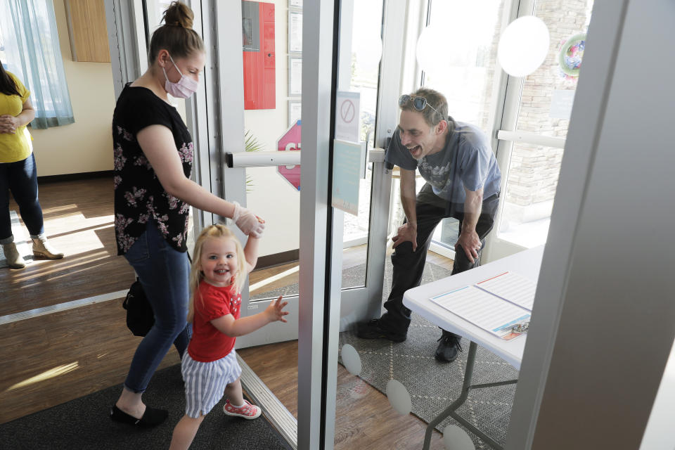 In this May 27, 2020 photo, Samantha Sulik, left, director of the Frederickson KinderCare daycare center, in Tacoma, Wash., looks on as Michael Canfield, right, waits in an entryway to pick up his daughter Aurora at the end of the day. As a precaution against the spread of the coronavirus, parents are not allowed to come into the building when they pick up their children. (AP Photo/Ted S. Warren)