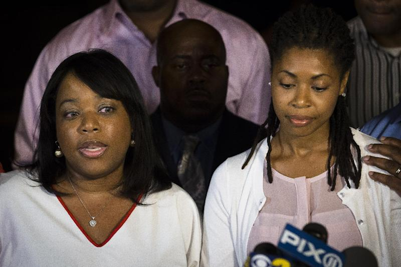 Valarie Carey, left, sister of Miriam Carey, speaks to the media outside her home beside her sister Amy in the Bedford-Stuyvesant neighborhood of Brooklyn, Friday, Oct. 4, 2013, in New York. Law-enforcement authorities have identified Miriam Carey, 34, as the woman who, with a 1-year-old child in her car, led Secret Service and police on a harrowing chase in Washington from the White House past the Capitol Thursday, attempting to penetrate the security barriers at both national landmarks before she was shot to death, police said. The child survived. (AP Photo/John Minchillo)
