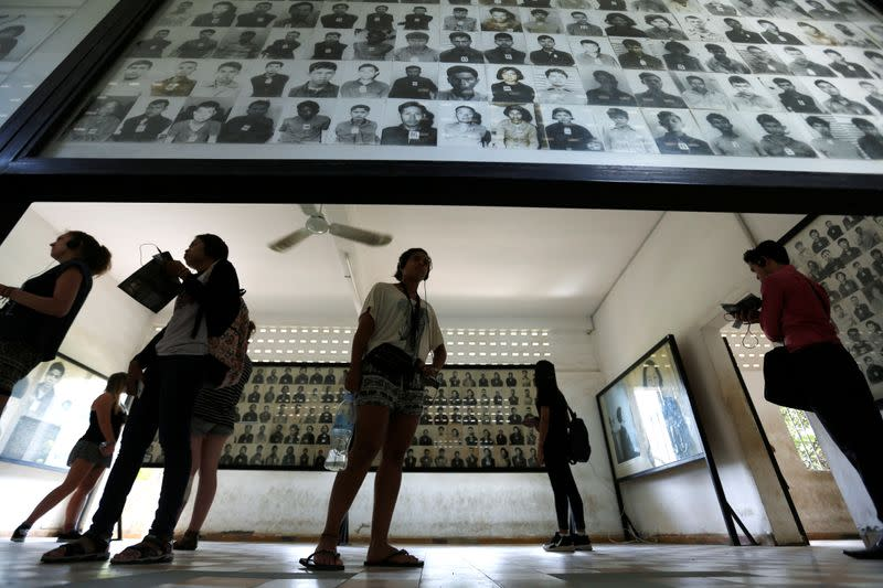 A visitor looks at pictures of victims of the Khmer Rouge regime at Tuol Sleng Genocide Museum in Phnom Penh