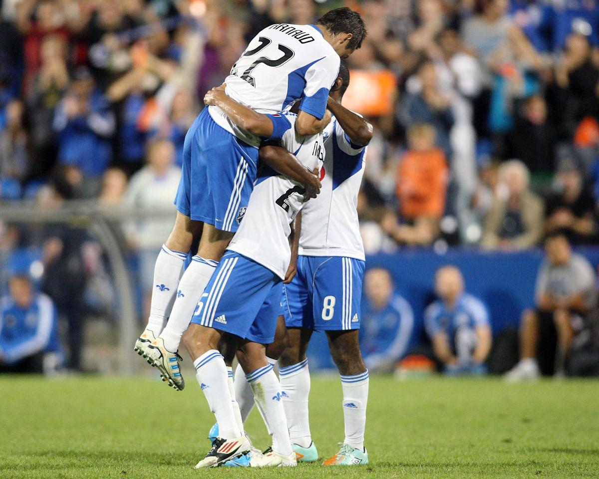 MONTREAL, CANADA - AUGUST 18:  Lamar Neagle #25 of the Montreal Impact celebrates his game winning goal with teammates during the match against the San Jose Earthquakes at the Saputo Stadium on August 18, 2012 in Montreal, Quebec, Canada.  The Impact defeated the Earthquakes 3-1.  (Photo by Richard Wolowicz/Getty Images)
