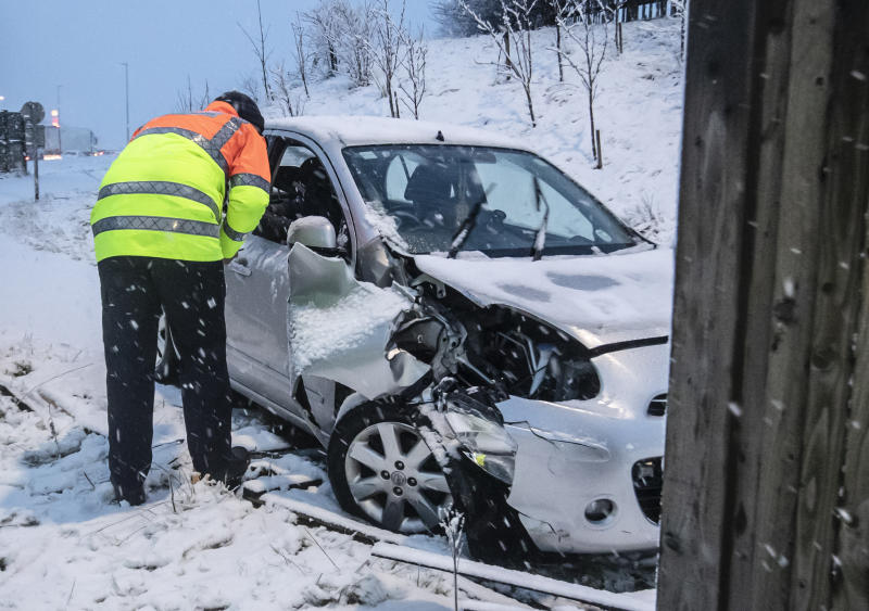 A traffic officer talks to the driver of a crashed car near Leeming Bar in North Yorkshire after overnight snow hit parts of the UK. (Photo by Danny Lawson/PA Images via Getty Images)