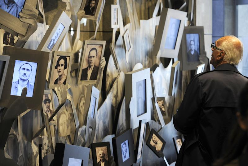 An elderly man looks at the portraits of Macedonian Jews who were killed in the Nazi extermination camp Treblinka, displayed in the Holocaust Memorial center of the Jews of Macedonia in the country's capital Skopje, on Thursday, April 19, 2012. Macedonia is marking the annual remembrance day for the six million Jews killed by the Nazis in World War II. (AP Photo/Boris Grdanoski)