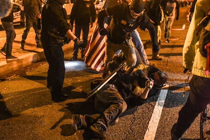 Members of the Proud Boys kick a member of Antifa on the ground during a protest on December 12, 2020 in Washington, DC. (Stephanie Keith/Getty Images)