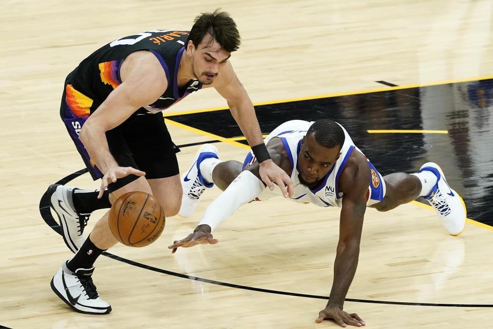 Phoenix Suns forward Dario Saric, left, and Denver Nuggets forward Paul Millsap chase down a loose ball during the first half of Game 2 of an NBA basketball second-round playoff series, Wednesday, June 9, 2021, in Phoenix. (AP Photo/Matt York)